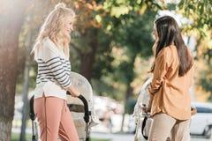 opinião lateral as mães de sorriso que olham se ao andar com carrinhos de criança de bebê imagens de stock