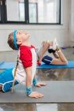 Opinião lateral as meninas bonitos no sportswear que exercitam em esteiras da ioga no gym Imagem de Stock Royalty Free