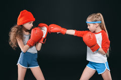 Opinião lateral as meninas desportivos que fingem o encaixotamento isolado no preto imagens de stock