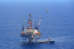 A opinião lateral do barco da plataforma petrolífera e da fonte de perfuração a pouca distância do mar Fotos de Stock Royalty Free