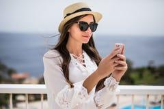 Opinião lateral do close-up uma jovem mulher de sorriso que usa um telefone celular fora foto de stock royalty free