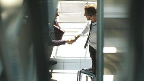 Opinião lateral do comprimento completo os homens de negócios que agitam as mãos no prédio de escritórios Fotos de Stock Royalty Free