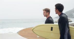 Opinião lateral dois surfistas masculinos que estão com a prancha na praia 4k video estoque