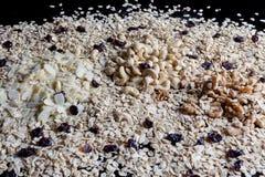 Opinião lateral dos ingredientes do Granola no fundo preto Fotos de Stock