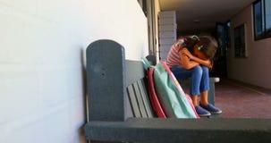 Opinião lateral a estudante afro-americano com cabeça abaixo do assento apenas no banco no corredor 4k da escola video estoque
