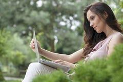 Opinião lateral a jovem mulher bonita que usa o portátil no parque fotos de stock royalty free