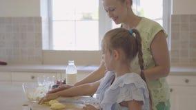 Opinião lateral a jovem mulher e sua filha pequena que cozinham bolos em casa na cozinha O trabalho e a elevação de terminação da filme