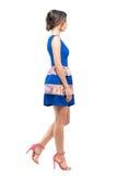 Opinião lateral a jovem mulher em anticipar de passeio do vestido curto azul sem mangas do verão Fotos de Stock Royalty Free