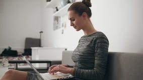 Opinião lateral a jovem mulher em casa que senta-se no sofá, trabalhando com um portátil e um texto de datilografia que olham rap vídeos de arquivo