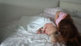 Opinião lateral a mamã nova bonita e seu bebê pequeno bonito que dormem na cama em casa filme