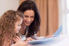 Opinião lateral a matriz e a filha que lêem um livro junto Imagens de Stock Royalty Free