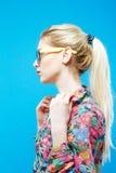 Opinião lateral a menina bonita com o rabo de cavalo que veste a camisa e monóculos coloridos no fundo azul no estúdio Foto de Stock Royalty Free