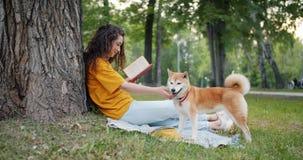 Opinião lateral a menina bonita que aprecia o livro no parque que sorri e que afaga o cão do puro-sangue video estoque