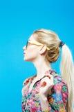 Opinião lateral a menina bonito com o rabo de cavalo longo que veste a camisa e monóculos coloridos no fundo azul no estúdio Foto de Stock