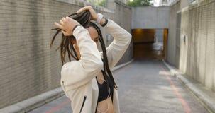Opinião lateral a mulher afro-americano nova que amarra seu updo na cidade 4k filme