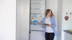 Opinião lateral a mulher bonita nova que está na cozinha ao olhar e ao tomar produtos do refrigerador filme