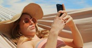 Opinião lateral a mulher caucasiano que usa o telefone celular em uma rede na praia 4k filme