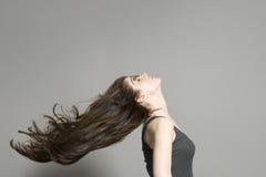 Opinião lateral a mulher com o cabelo longo que funde no vento Imagem de Stock Royalty Free