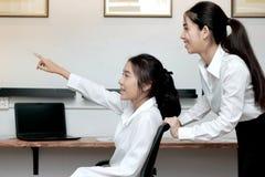 Opinião lateral a mulher de negócio asiática alegre que tem o divertimento junto no escritório imagem de stock