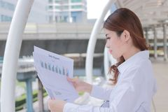 Opinião lateral a mulher de negócio asiática nova atrativa que analisa o documento ou as cartas em suas mãos no escritório exteri Imagens de Stock Royalty Free