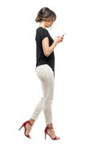 Opinião lateral a mulher de negócio ocupada no terno formal que anda e que datilografa no telefone celular Foto de Stock