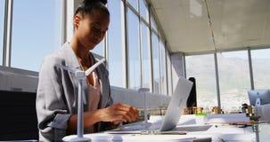 Opinião lateral a mulher de negócios afro-americano que usa o portátil na mesa em um escritório moderno 4k filme