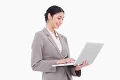 Opinião lateral a mulher de negócios que usa o portátil Fotos de Stock