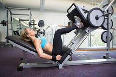 A opinião lateral a mulher do ajuste que faz o pé pressiona no gym Fotos de Stock