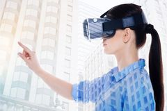 Opinião lateral a mulher em auriculares de VR que aponta com dedo fotos de stock royalty free