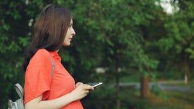 A opinião lateral a mulher gravida atrativa que anda no parque e que usa o telefone esperto, pessoa está olhando a tela então olh filme