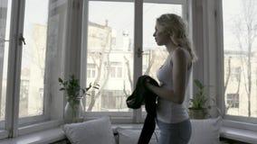 Opinião lateral a mulher loura nova e bonita na calças de ganga e na camiseta de alças branca que decolam o casaco de lã preto a? filme