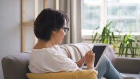 A opinião lateral a mulher madura está usando a tabuleta que senta-se no sofá em casa video estoque