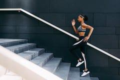 Opinião lateral a mulher no sportswear que corre acima as etapas na cidade imagens de stock royalty free