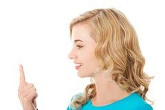 Opinião lateral a mulher que olha em seu dedo Imagem de Stock Royalty Free