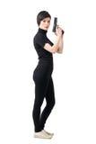 Opinião lateral mulher resistente armada que guarda a arma que olha a câmera imagens de stock