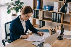 opinião lateral o advogado fêmea que faz o documento no local de trabalho com portátil Imagens de Stock Royalty Free