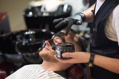 Opinião lateral o barbeiro que põe a máscara preta sobre a cara de masculino imagens de stock