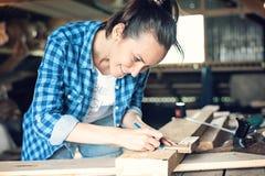 Opinião lateral o carpinteiro fêmea de sorriso a marcar em um corte da serra da faixa do lápis da placa de madeira Imagem de Stock Royalty Free