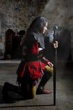 Opinião lateral o cavaleiro em Armor With Sword Praying na igreja velha fotografia de stock royalty free