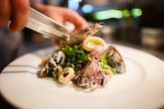 A opinião lateral o cozinheiro chefe que cozinha a salada do marisco consistiu na alface, nos círculos da cebola, nos mexilhões e Foto de Stock