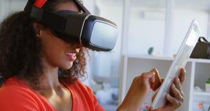 Opinião lateral o desenhador de moda fêmea africano americano que usa auriculares da realidade virtual e o tabl digital vídeos de arquivo