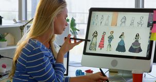 Opinião lateral o desenhador de moda fêmea caucasiano que fala no telefone celular no escritório 4k video estoque