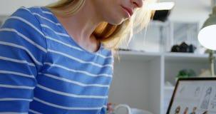 Opinião lateral o desenhador de moda fêmea caucasiano que trabalha na mesa no escritório 4k video estoque