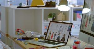 Opinião lateral o desenhador de moda fêmea caucasiano que trabalha no computador na mesa no escritório 4k video estoque