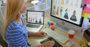 Opinião lateral o desenhador de moda fêmea caucasiano que usa a tabuleta gráfica na mesa no escritório 4k video estoque