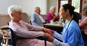 Opinião lateral o doutor fêmea caucasiano que consola a mulher superior deficiente triste no lar de idosos 4k video estoque