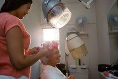 Opinião lateral o esteticista que ajusta encrespadores no cabelo superior da mulher imagem de stock royalty free