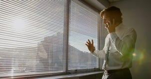 Opinião lateral o executivo masculino caucasiano novo que fala no telefone celular perto da janela no escritório moderno 4k filme