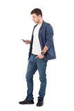 Opinião lateral o homem à moda novo nas calças de brim usando o telefone celular fotos de stock