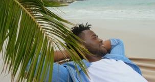 Opinião lateral o homem afro-americano que relaxa em uma rede na praia 4k video estoque
